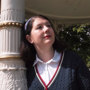 Eleanor Harkstead leans against the ornamental 19th C supporting pole of a bandstand in the park.