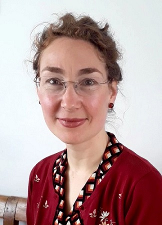 A photo of Ruth. She is smiling, she's wearing glasses and a bright red cardigan.
