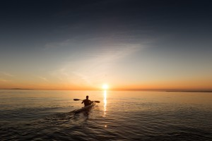 Person canoeing towards sunset